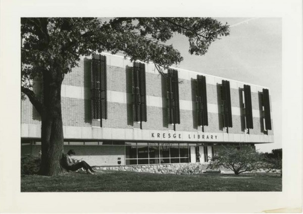 Exterior of Kresge Library with a student sitting underneath a t
